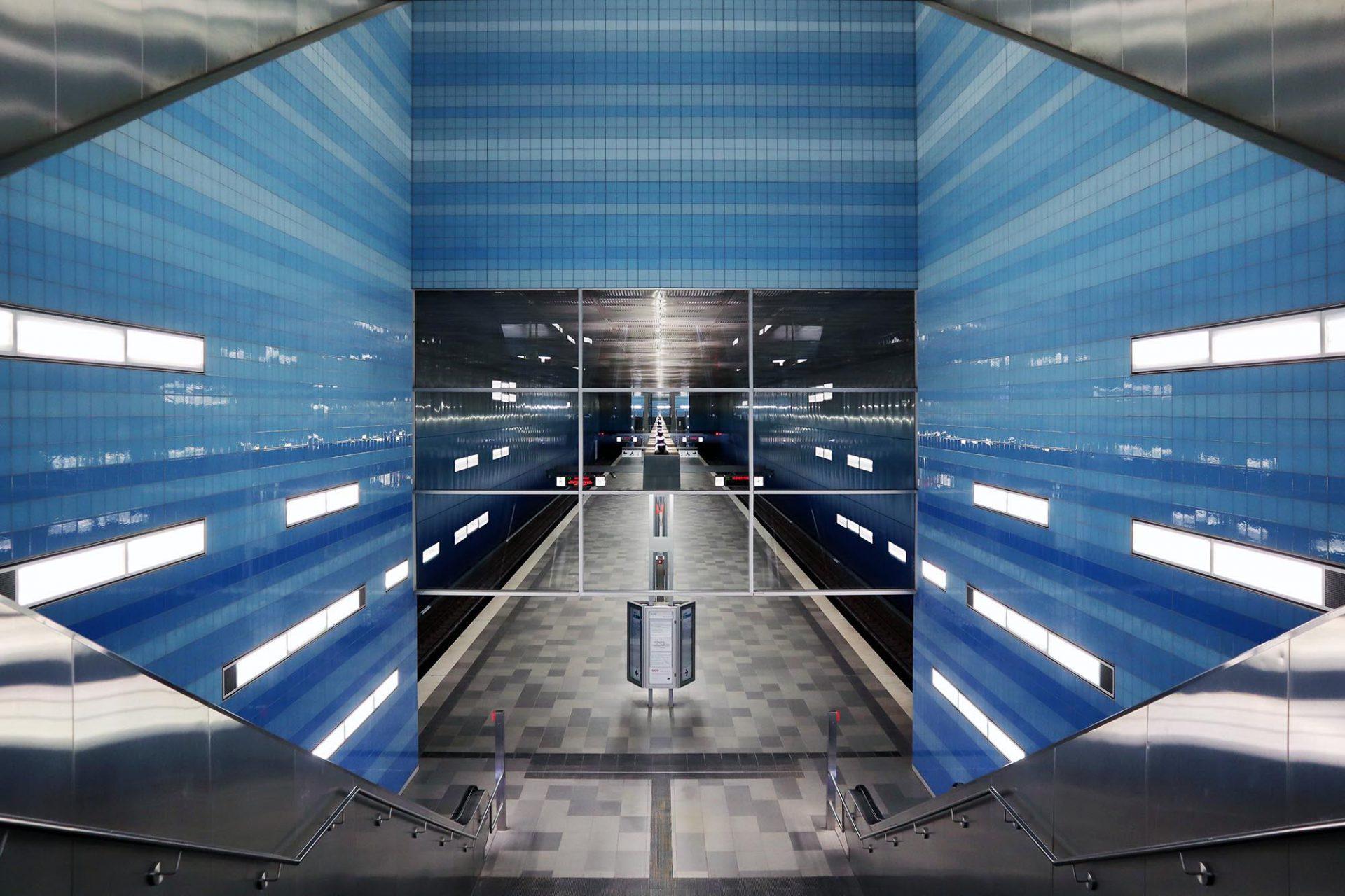 U-Bahnhof Überseequartier. Entwurf: netzwerkarchitekten. Fertigstellung: 2012. Die Darmstädter Architekten inszenierten den Bahnhof wie eine abstrakte Unterwasserwelt. Die Decke am Bahnhof ist aus Edelstahlkassetten mit Lochung, die an die Bewegung einer Wasseroberfläche erinnern sollen. Die Wandverkleidung ist aus Edelstahl, digital bedruckt mit einem Blauverlauf. Der Bodenbelag ist aus Betonwerkstein, der an eine helle Sandbank angelehnt ist.