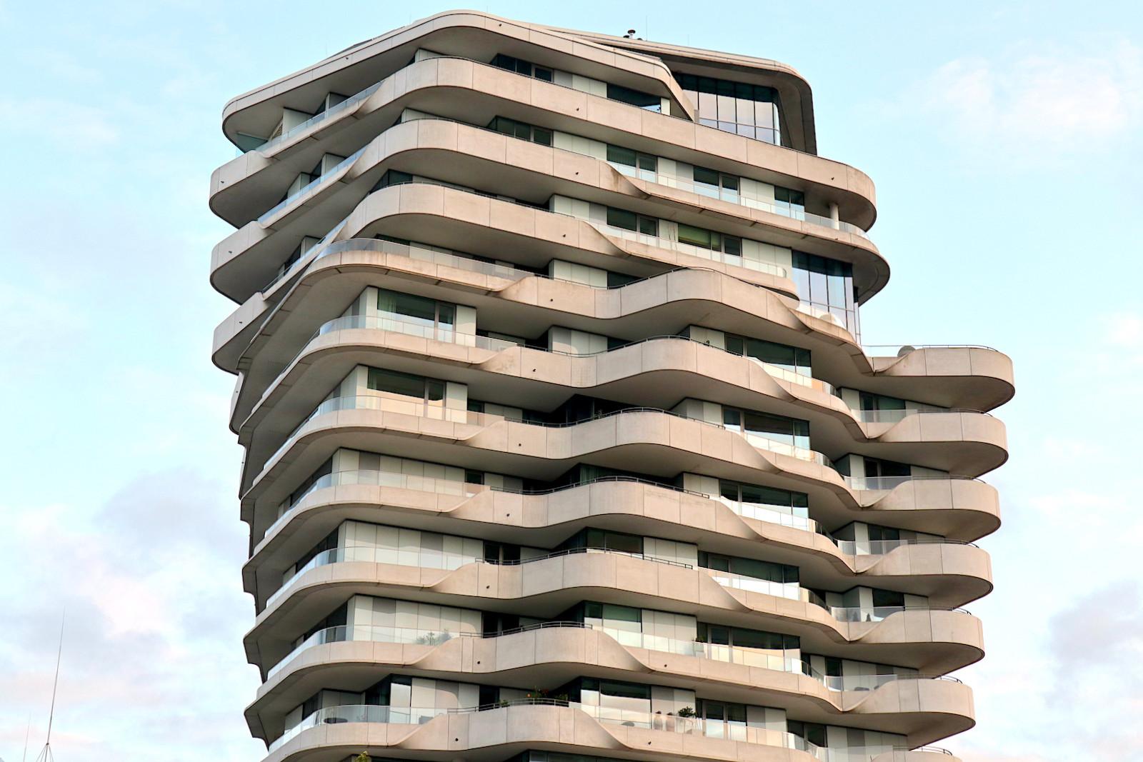 Marco-Polo-Tower. Entwurf: Behnisch Architekten, Stuttgart. Fertigstellung: 2009. Der 55 Meter hohe Wohnturm steht für hochwertig-hochpreisiges Wohnen in der Innenstadt. Bei der Stahlbetonskelettkonstruktion ist jedes Geschoss um ein paar Grad um die Achse des Kerns gedreht, so dass sich dadurch mit dem reduzierten Äußeren ein skulpturaler Eindruck ergibt, der Kritiker mal an einen Trichter, mal an einen Dönerspieß erinnert.
