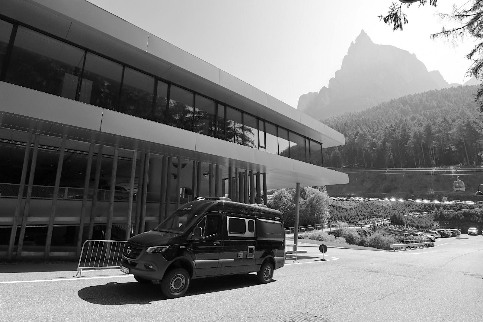 Parkhaus an der Talstation Seiser Alm Bahn. Entwurf: Lukas Burgauner. Fertigstellung: 2013. Unweit der Talstation hat Burgauner zudem einen Neubau geschaffen, der Parkhaus sowie Firmensitz eines Busunternehmens ist mit Werkstatt, Waschstraße, Büros und Unterkünften für Angestellte.