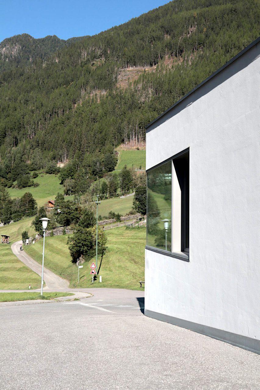 Haus am Bühel, St. Jakob. Den Neubau integrierten sie als hell-skulpturalen Baukörper mit Einschnitten im Eingangsbereich, die zugleich wettergeschützte Nischen bilden. Auf der anderen Seite befindet sich eine offene Bühne, die von Kindern (des Dorfes oder des Hotel Bühelwirt) gerne als Platz zum Toben und Rennen genutzt wird.