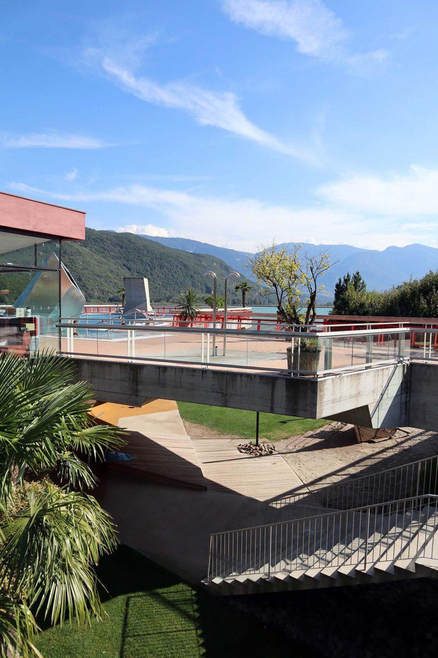 Seebad Kaltern. Beide Ebenen sind durch eine Sitz-Liege-Tribüne verbunden. Beeindruckend ist die skulpturale Betonkonstruktion und die runden Öffnungen im Boden des Sportbeckens. Für die Statik des Tragwerks waren die Fachleute vom Ingenieursbüro Bollinger und Grohmann verantwortlich.