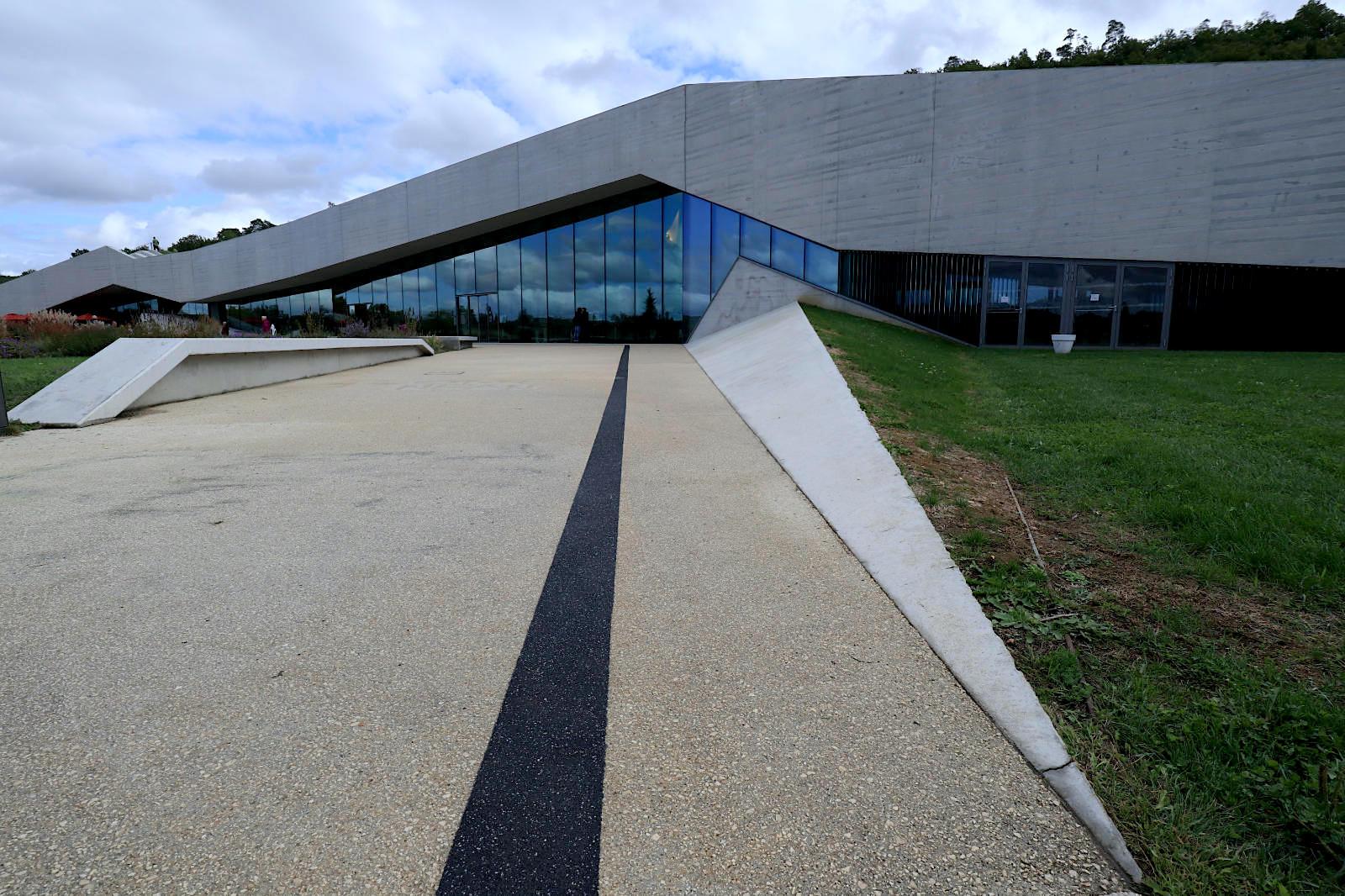 Centre International de l'Art Pariétal. Das Bauwerk scheint wie aus dem Hügel gegraben. Die gläserne Front und der alternierende, breite Betonsturz wirken wie ein stilisiertes Landschaftsmotiv.