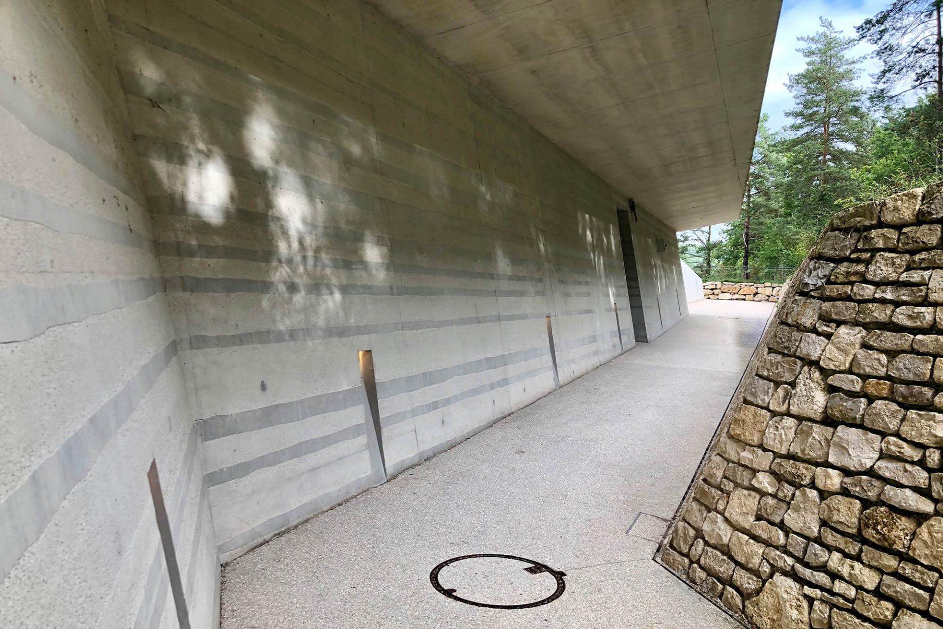 Centre International de l'Art Pariétal. Natursteinwände kontrastieren mit Betonwänden, deren Oberflächen so bearbeitet wurden, das sie einen Verweis auf die Schichtung des Bodens geben.