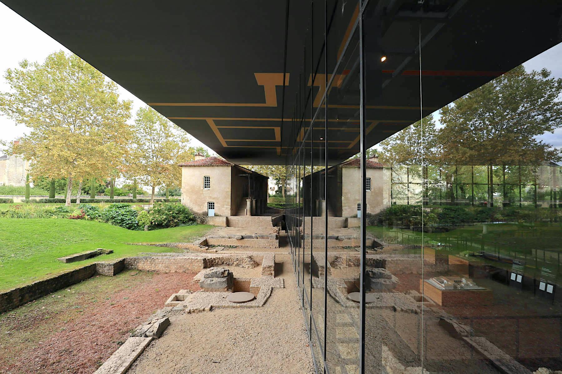 Musée Vésunna. Entwurf: Jean Nouvel, 2003. Bäume und Bauwerke spiegeln sich an den Glaswänden und tragen so zur Magie des Ortes bei. Das kleine Haus neben der Ruine wurde im 18. Jahrhundert errichtet. Es war einst der Arbeitsplatz des ersten Archäologen, der an den Ausgrabungen von Vésunna arbeitete. Nouvel ließ es zusammen mit Philippe Oudin, dem lokalen Leiter der historischen Gebäude, restaurieren.