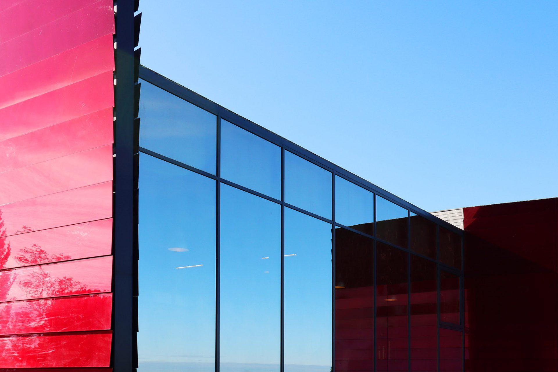 Château La Dominique. Die abgedunkelte Glasfront, hinter der die dreiundzwanzig konischen Tanks aus Edelstahl nur schemenhaft zu erkennen sind, wirkt wie ein Spiegel, in dem die Kulturlandschaft reflektiert wird.