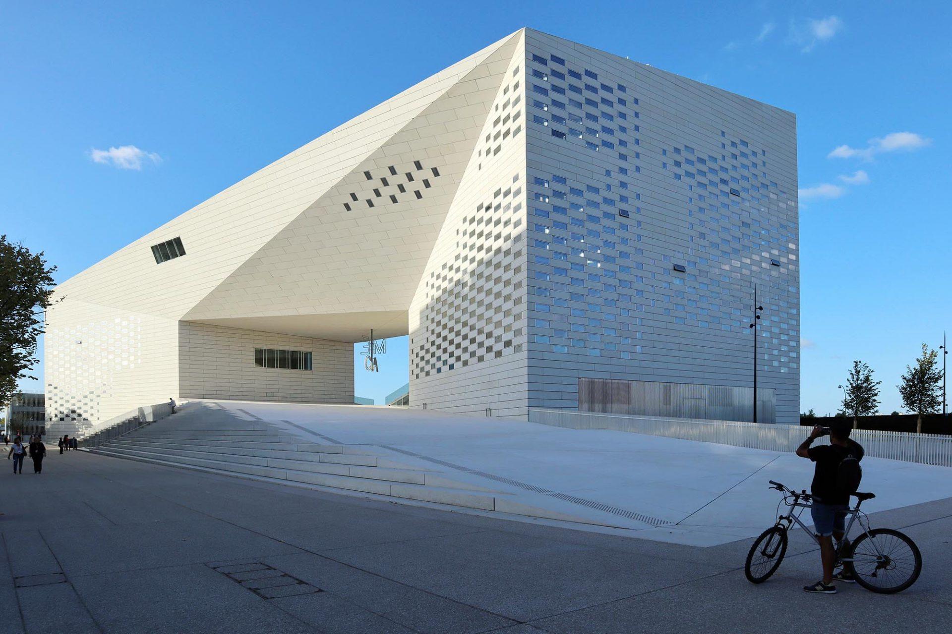 """La Méca (""""Maison de l'Économie Créative et de la Culture""""). Entwurf: BIG, 2019. Der monolithisch wirkende Baukörper mit seinen eingestreuten Fensteröffnungen ist mit vorfabrizierten Betonelementen verkleidet."""