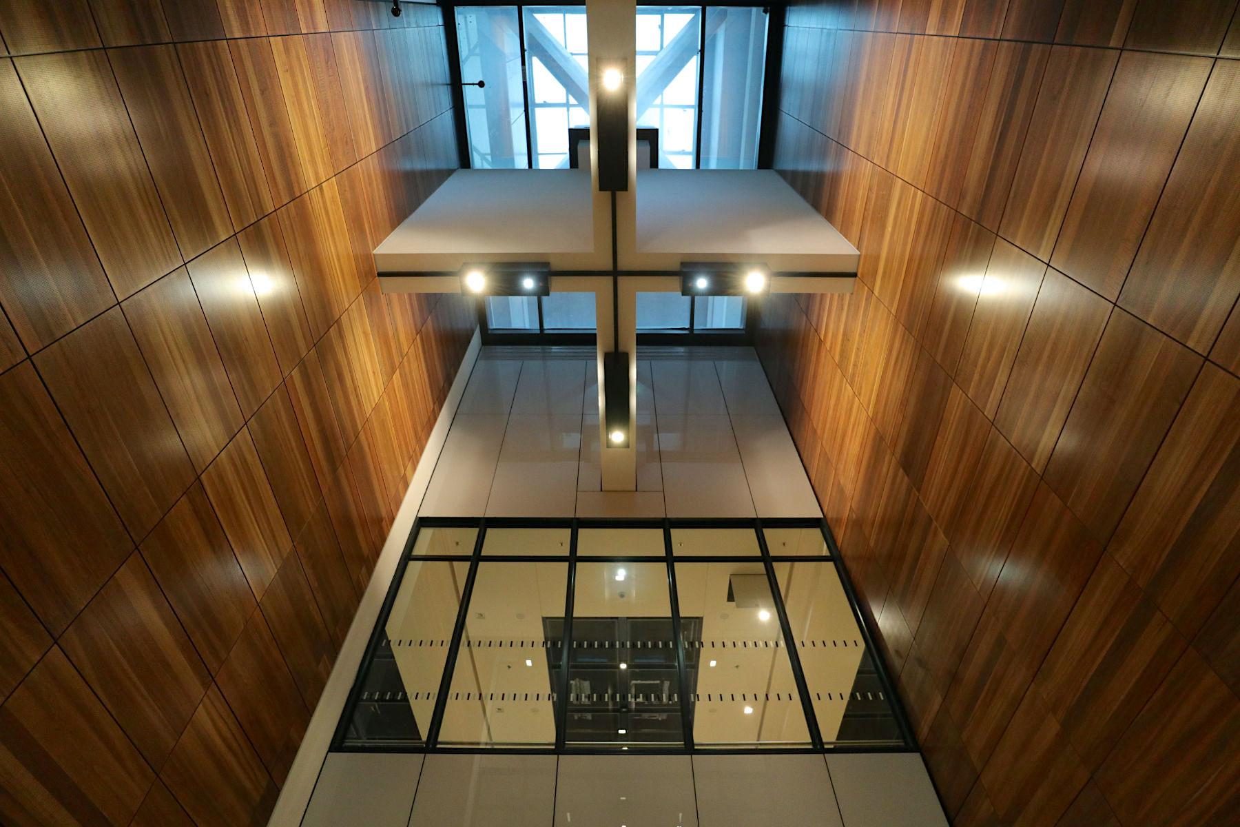 Flughafen Berlin Brandenburg BER. Strenge Symmetrien, Kolonnaden, eine Materialmischung aus Nussbaumholz, Juramarmor, Glas und Beton und das Riesenflachdach sind die zentralen Elemente der BER-Architektur am Hauptterminal.
