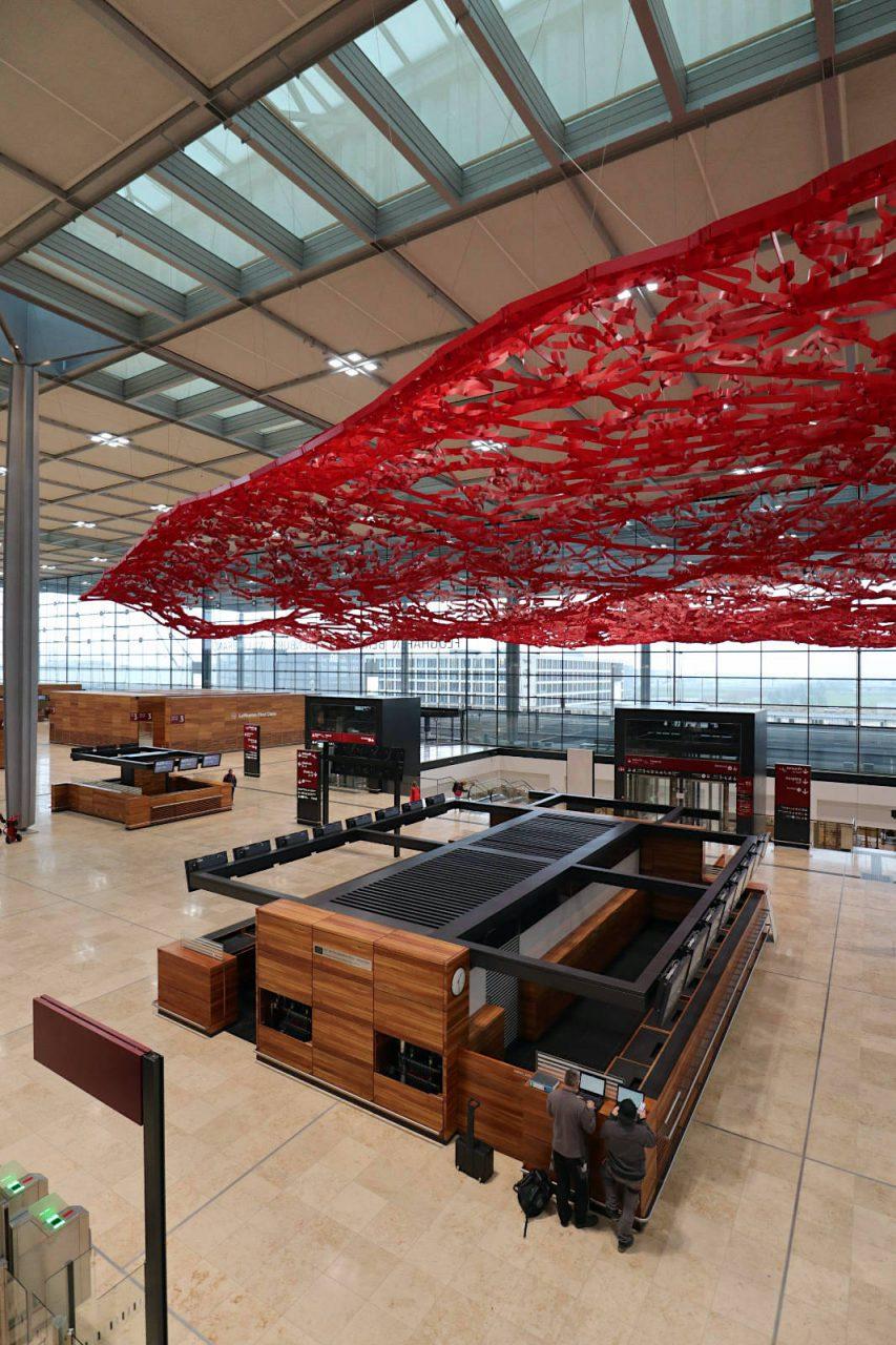 """Flughafen Berlin Brandenburg BER. Berlin als Stadt der Kreativen sollen Fluggäste auch am BER erleben. Sechs internationale Künstler haben sich mit dem Thema """"Luft– Land"""" auseinandergesetzt und jeweils ein Kunstwerk am Flughafen geschaffen. Die Künstlerin Pae White aus Kalifornien gestaltete den großen, roten Teppich aus Metallgewebe."""