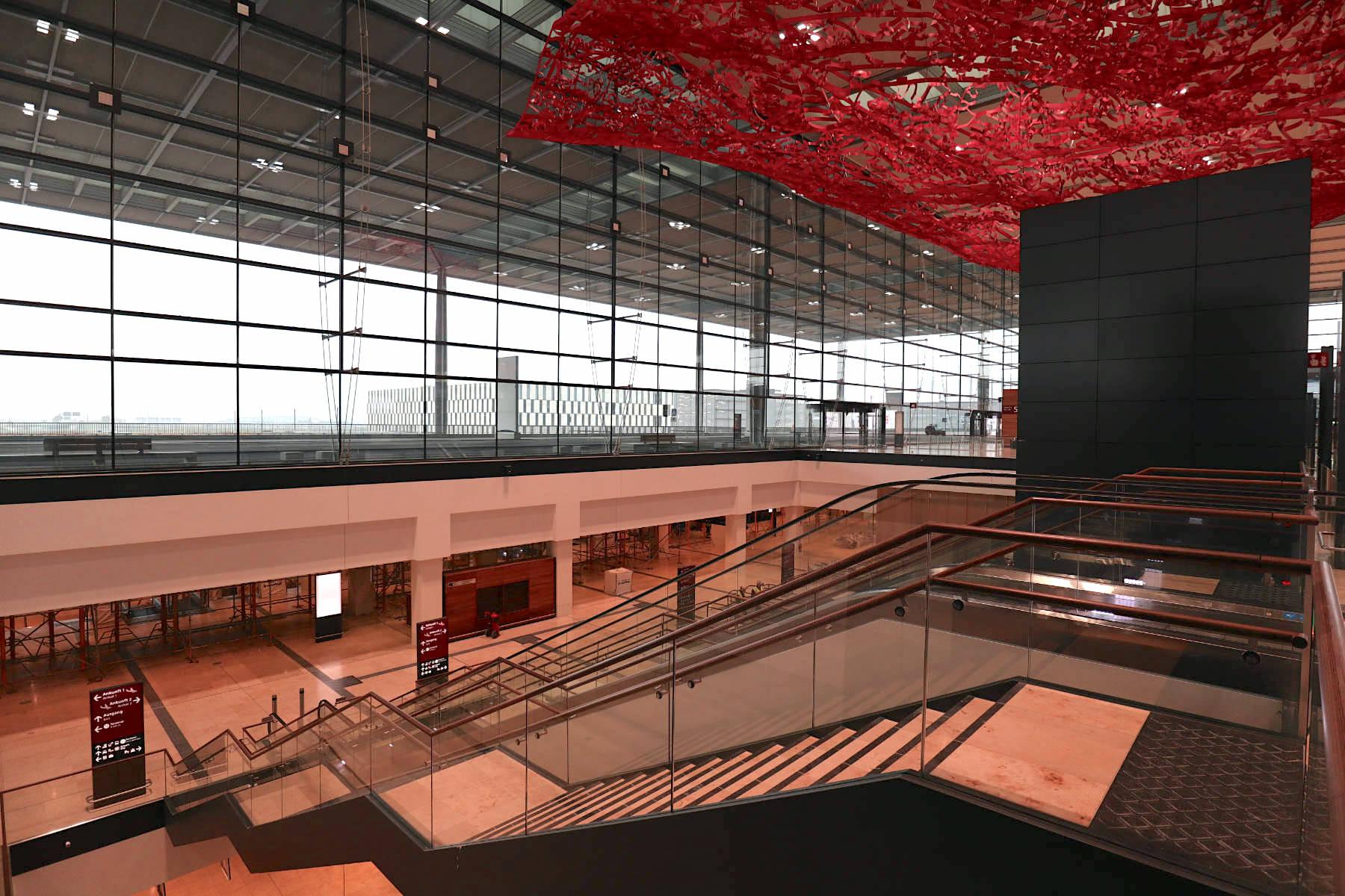 Flughafen Berlin Brandenburg BER. Der Übergang vom Flughafenbahnhof und der Haupthalle. Oben: die Installation Magic Carpet.