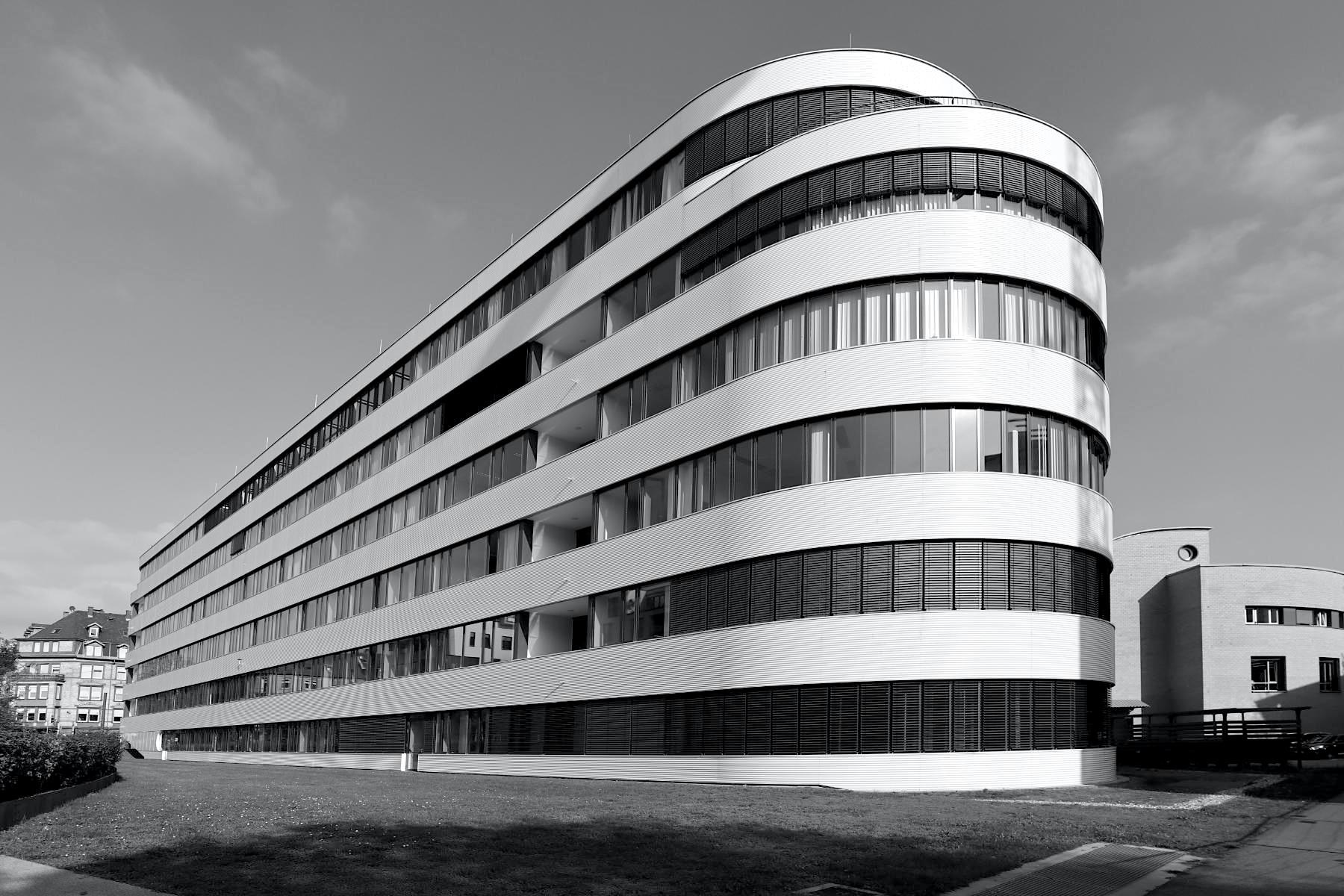 Bürogebäude Synus. Entwurf: Kramm Strigl, 2014. Der Bau ist mehrfach gerundet und in der Höhe mehrfach gestaffelt. Das Gebäude mit 9.400 m2 Bürofläche ist Green Building-zertifiziert, die Architekten aus Darmstadt legten wert auf hohe Energieffizenz durch Fernwärme sowie ein flexibles und praktisches Büorkonzept für die über 200 Angestellten.