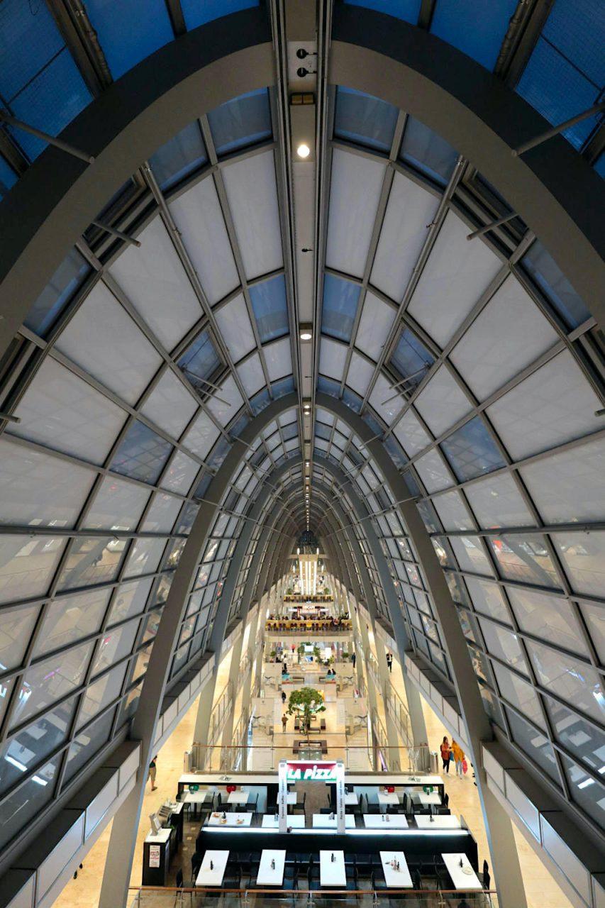 Ettlinger Tor. Entwurf: Jost Hering, Klaus Maria Hoffmann, 2005. Es ist eines der größten Einkaufszentren Südddeutschlands mit 130 Geschäften auf einer Gesamtfläche von fast 40.000 qm. Die Passage mit den Läden wird von einem 130 m langen Glasgewölbe überdacht, inspiriert von Glaspassagen des 19. Jahrhunderts.