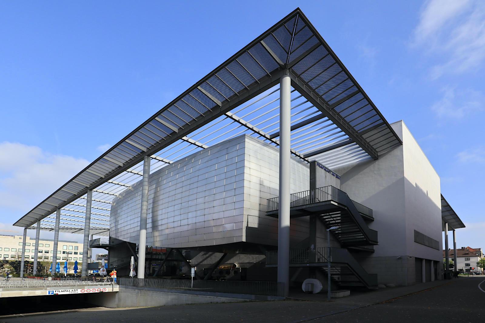 Filmpalast am ZKM. Entwurf: Till Sattler, 2000. Das Multiplex-Kino bildet mit dem gegenüber befindlichen ZKM einen großen Platz abseits der lauten, mehrspurigen Brauerstraße. Wichtige Merkmale sind das weit auskragende Vordach und die technisch-anmutende Gestaltung mit der Verkleidung aus Edelstahlplatten. Weitere Kinopaläste hat der Kölner Architekt Sattler in Düsseldorf und Frankfurt realisiert.