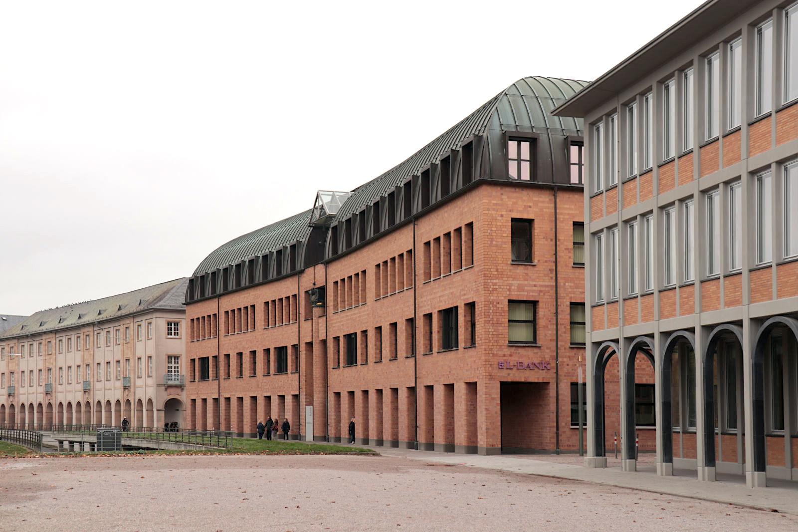Landeskreditbank Baden-Württemberg L-Bank. Entwurf: Heinz Mohl, 1983. Das postmoderne, dreigeschossige Gebäude mit der Klinkerfassade an prominenter Stelle am Schlossplatz fügt sich in die vorhandene Nachbarschaft. Gleichzeitig betonte Mohl mit dem tiefen und hohen Fassadeneinschnitt die Eigenständigkeit seines Baus.