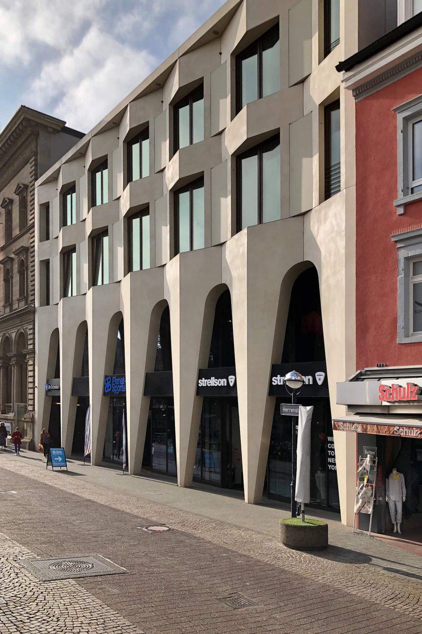 Wohn-, Büro- und Geschäftshaus. Entwurf: Lederer Ragnarsdóttir Oei, 2013. Im Vorgängerbau hatte Götz Werner mit dem ersten dm-Drogeriemarkt sein Unternehmen begonnen. Die Fassade des Neubaus besteht aus Betonfertigteilen. Diese sind in einem hellen Sandton gefärbt und wirken nahezu fugenlos.