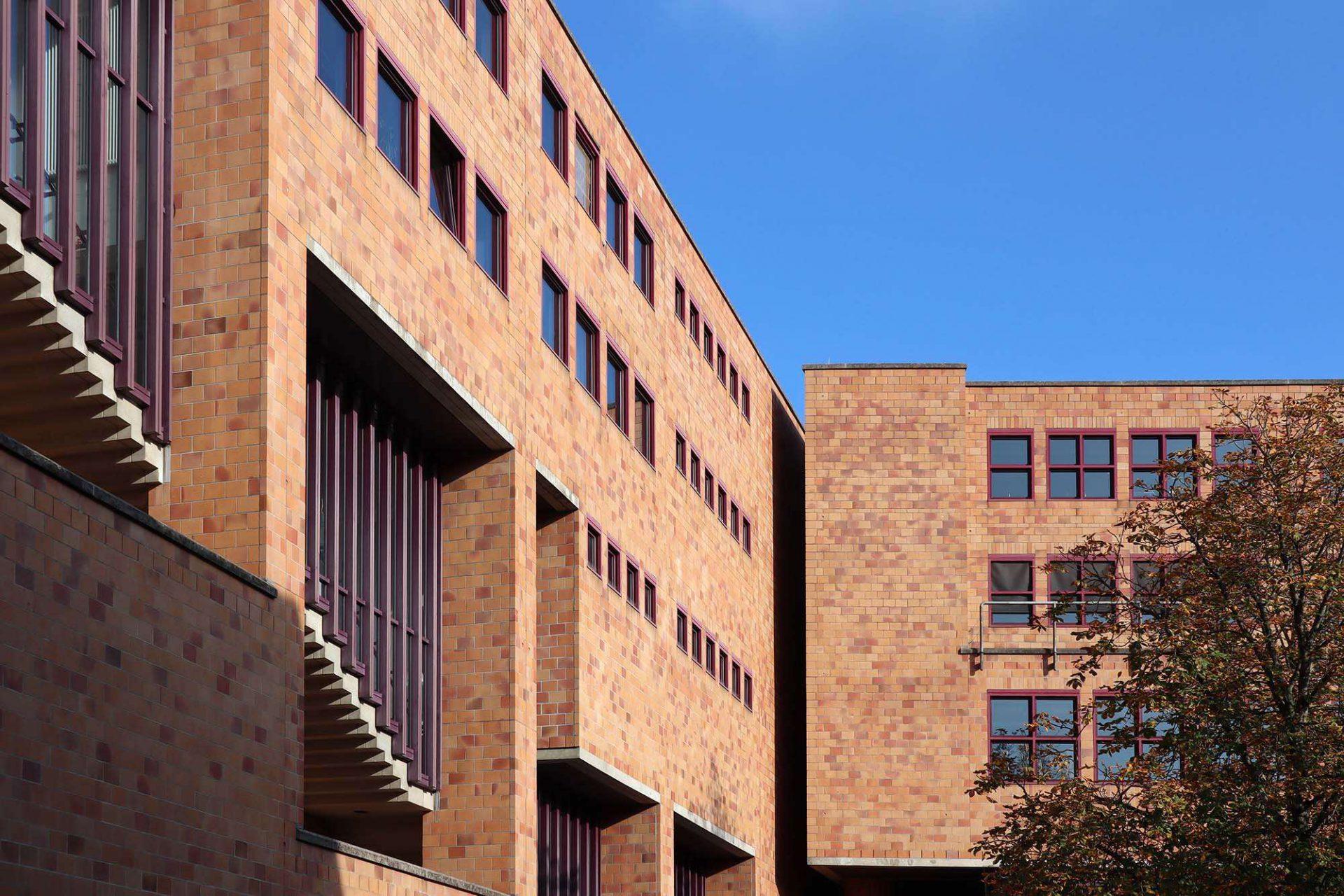 Heinrich-Hübsch-Schule. Die Nebenräume sind zu den (verkehrsreichen) Straßen ausgerichtet und haben asymmetrische Fassaden. So sind hier Außentreppen sichtbar. Die Verklinkerung verweist auf die durch Heinrich Hübsch (1795–1863, Architekt und großherzöglicher Baubeamter in Karlsruhe) begründete Tradition der Ziegelbauten.