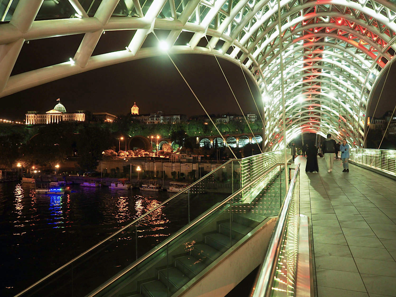 Illumination. Kaum eine Sehenswürdigkeit bleibt ausgespart von der Lichterflut bis tief in die Nacht. Vor allem die Friedensbrücke, nach den Plänen von Michele De Lucchi 2010 aus Stahl und Glas in einem eleganten Schwung über den Mktvari gezogen, zieht mit Lichtkaskaden aus zehntausenden LEDs die Blicke auf sich.