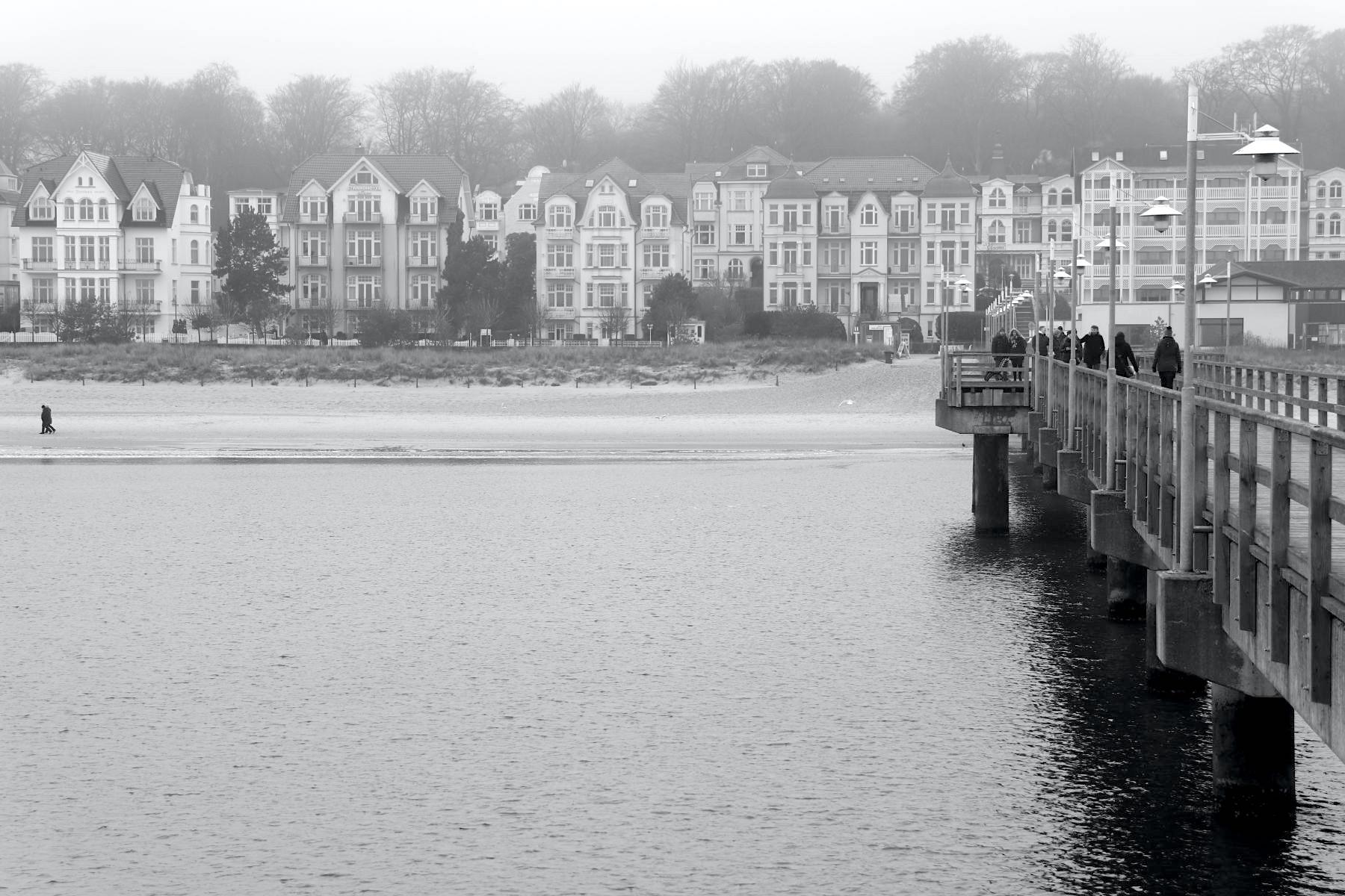 """Bansin. Nordöstlich von Heringsdorf entstand 1897 das jüngste der drei Bäder. Es liegt in einem schmalen Streifen direkt zwischen der Steilküste und der See. Die Häuser wurden """"auf Lücke"""" gebaut, sodass auch die zweite Reihe direkt auf das Meer blickt. Der Seesteg hier ist schlicht und bescheiden."""
