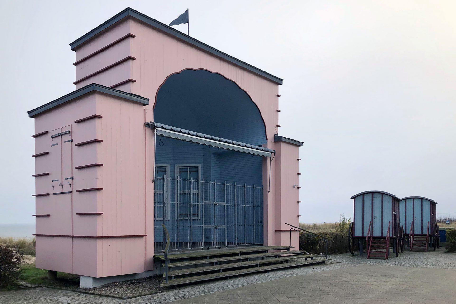 """Bansin. Die """"Kurmuschel"""" mit dem Konzertplatz wurde 1932 mit einem Pfingstkonzert eröffnet und ist heute denkmalgeschützt. Zu beiden Seiten stehen Nachbauten der historischen Badekarren, in denen die Badegäste mit vorgespannten Pferden zur See gebracht wurde."""
