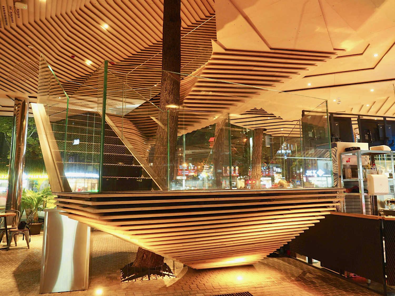 Bauen im Kontext. Einer der erfolgreichsten unter den jungen Baumeistern ist Giorgi Khmaladze, der in Harvard studiert und bei Michele De Lucchi gearbeitet hat. Mit seiner Architektur nimmt er gerne Bezug auf die Umgebung. So hat er 2017 für einen Burgerladen an der belebten Merab Kostava Straße einen kleinen Kiefernwald mit Stahlskelett und Sperrholz umbaut. Auf der Dachterrasse spenden die Baumkronen Schatten.