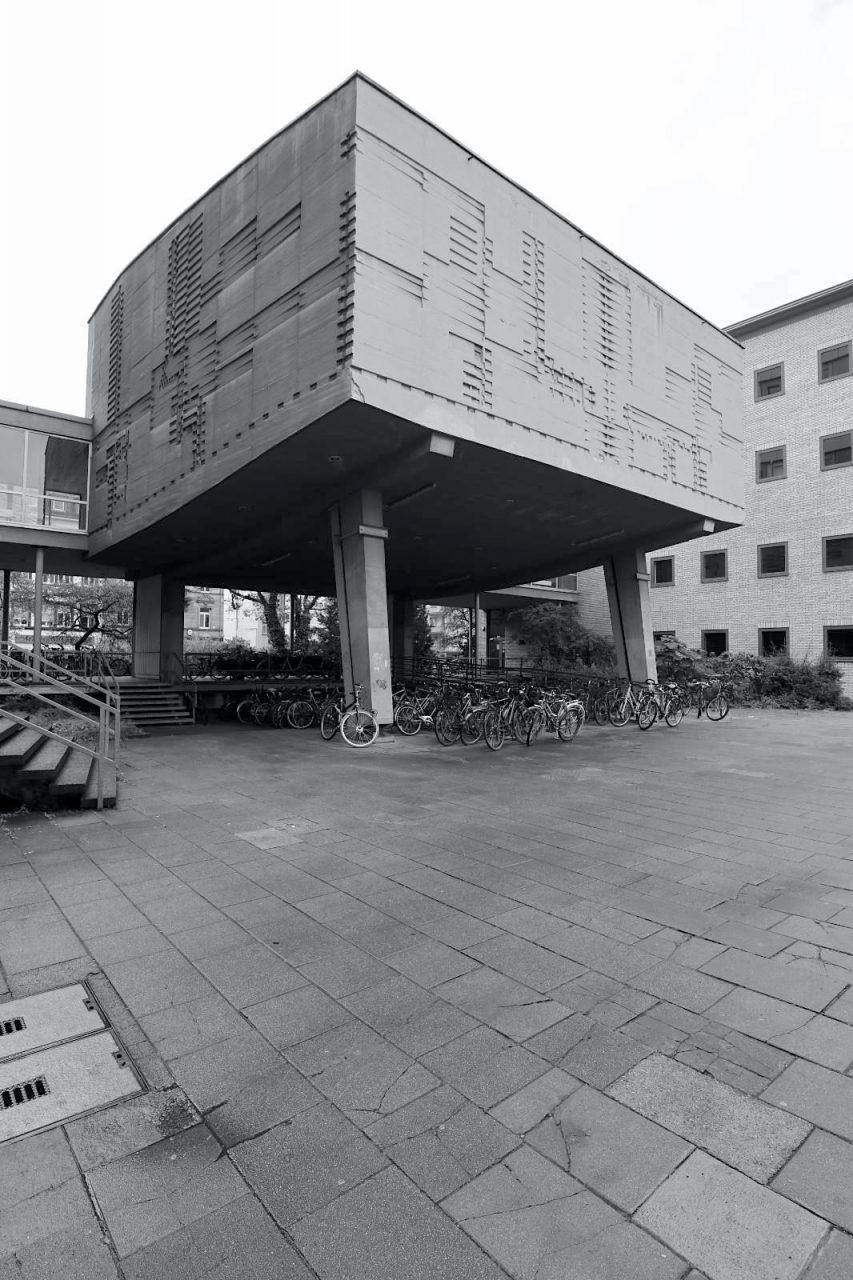 Nusselt-Hörsaal. Der kantige Betonbau auf Stelzen war viele Jahrzehnte der Hörsaal der Maschinenbauer. Arnold versah die Betonkapsel mit einem Relief aus Linien und Einkerbungen, die den Bau noch skulpturaler und UFO-ähnlicher machen. Seit 2009 ist der Hörsaal wegen Baufälligkeit gesperrt. Im Zuge der Entwicklung des Campus Süd soll der Hörsaal (Uni-Gebäude Nr. 10.23) abgerissen werden, ein Neubau für das Lern- und Anwendungszentrum Mechatronik wird hier entstehen.