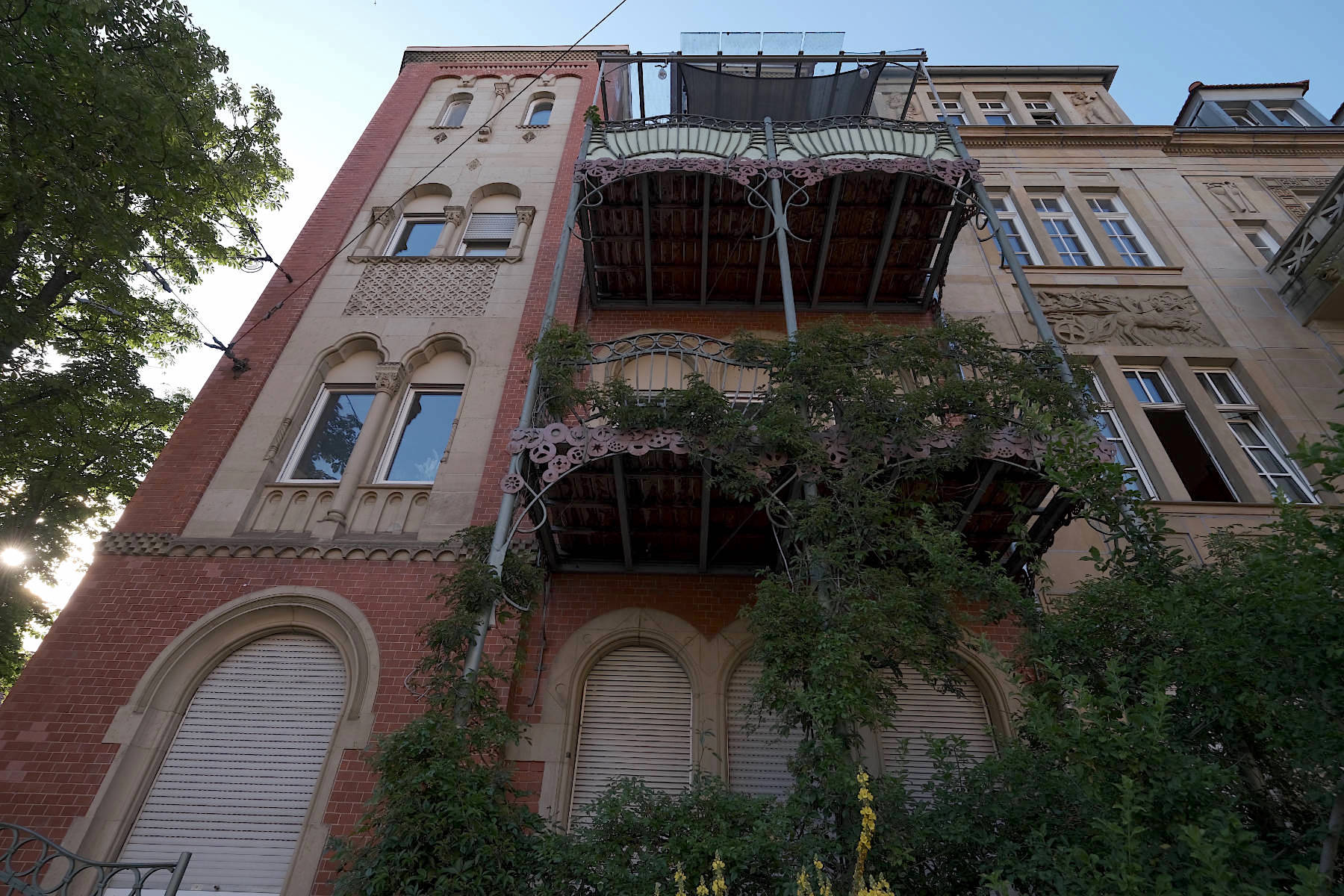 Karlsruher Jugendstil. Rot-sandfarbene Fassade mit expressiver Balkongestaltung an einem Wohnhaus am Karl-Wilhelm-Platz.